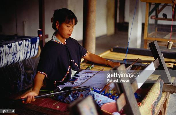 Woman weaving on traditional loom in workshop that produces traditional Ikat and Songket woven fabrics, Sukarara village, Lombok, West Nusa Tenggara, Indonesia, South-East Asia