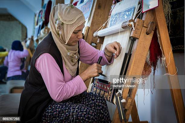 Woman weaving silk carpet on traditional loom