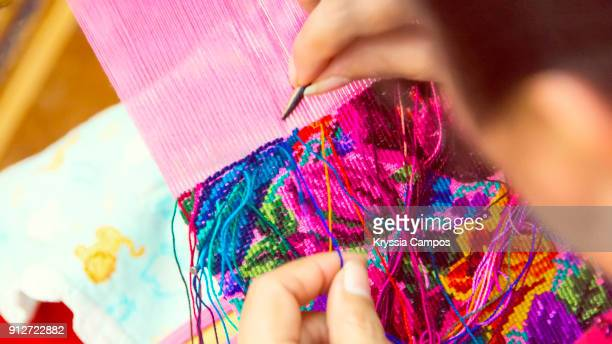 woman weaving with a backstrap loom at handicraft market - loom stock pictures, royalty-free photos & images