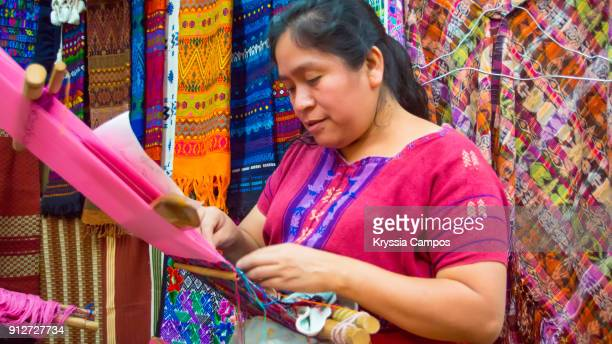 woman weaving with a backstrap loom at handicraft market - guatemala stock pictures, royalty-free photos & images