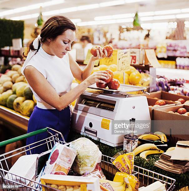 Woman weighing fresh tomatoes at grocery store