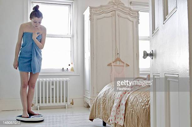 woman weighing herself at home - mass unit of measurement stock pictures, royalty-free photos & images