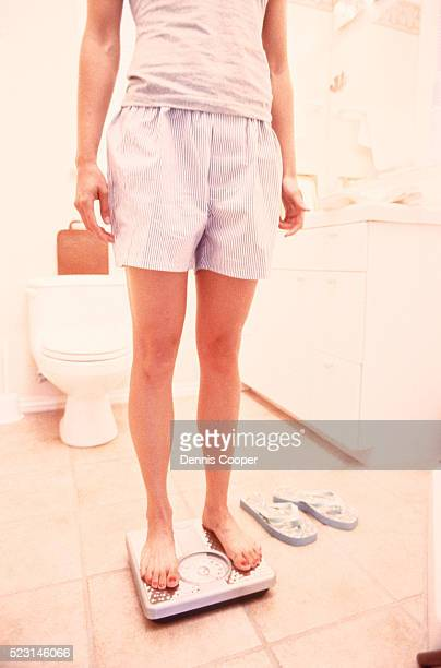 Woman weighing herself in the bathroom