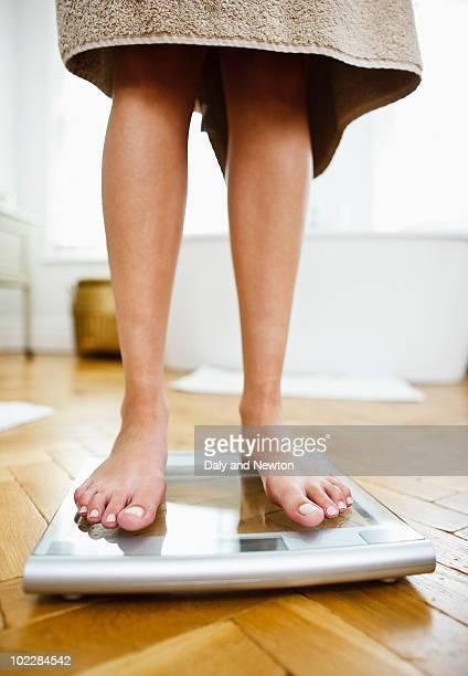 Woman weighing herself on bathroom scales