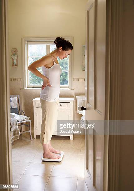 woman weighing herself on bathroom scales. - 短めのパンツ ストックフォトと画像