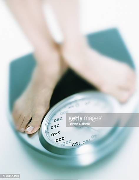 woman weighing herself on scale - image stock pictures, royalty-free photos & images