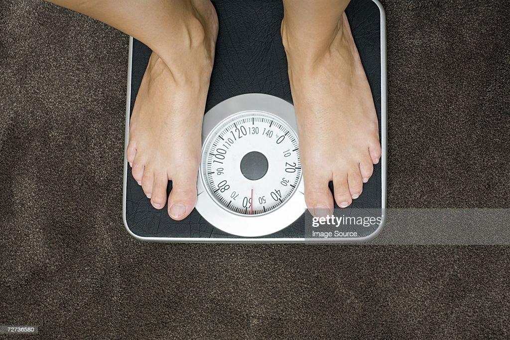 Woman weighing herself : Stock Photo