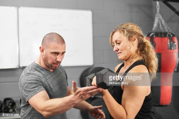 Woman weightlifting in gym with personal trainer