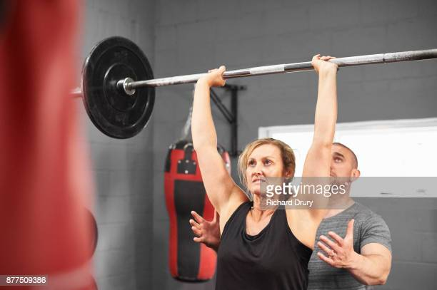 Woman weightlifting with personal trainer
