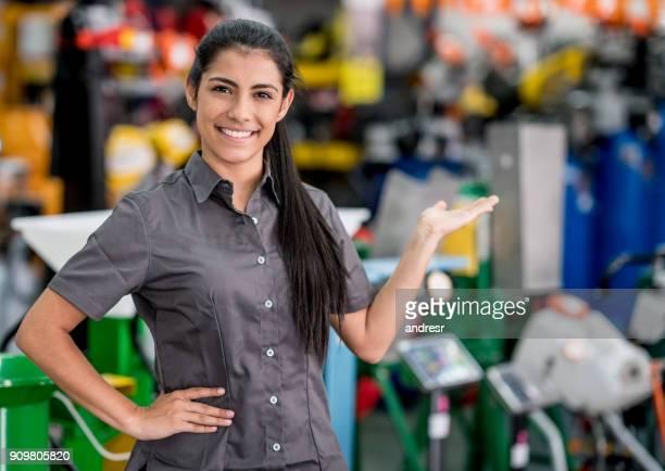 Mujer, bienvenida a los clientes en un almacén del hardware