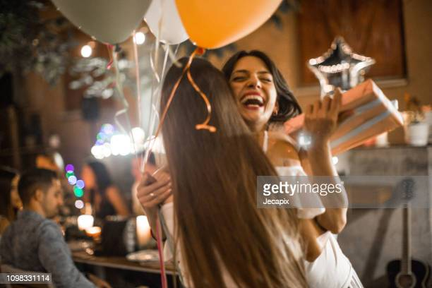 woman welcoming guest on her birthday dinner party and recieving gifts - happy birthday stock pictures, royalty-free photos & images