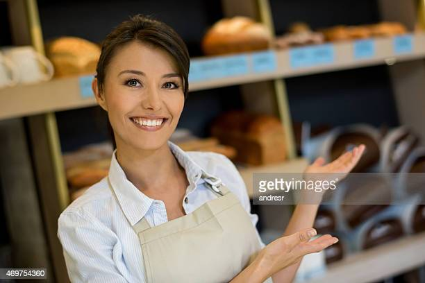 Woman welcoming people into a bakery