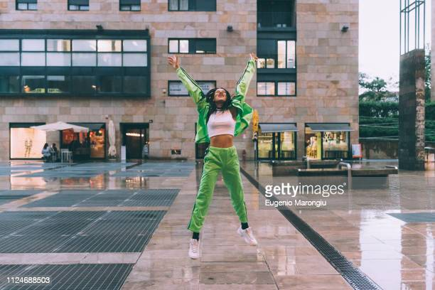 woman welcoming rain in town square, milan, italy - crop top stock pictures, royalty-free photos & images