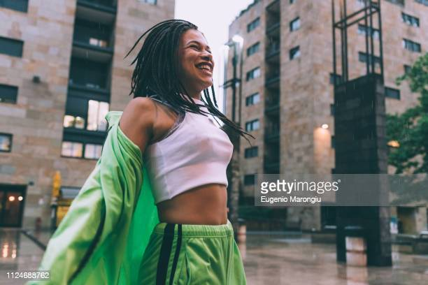 woman welcoming rain in town square, milan, italy - スポーツウェア ストックフォトと画像