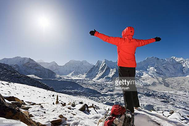 Woman welcoming sunrise on a mountain, Mount Everest National Park