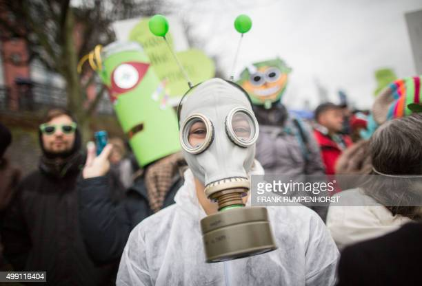 Woman weras a gas mask while taking part in a demonstration organised by environmental NGOs on November 29, 2015 in Frankfurt am Main, central...