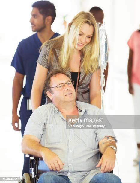 Woman wheeling father in hospital hallway