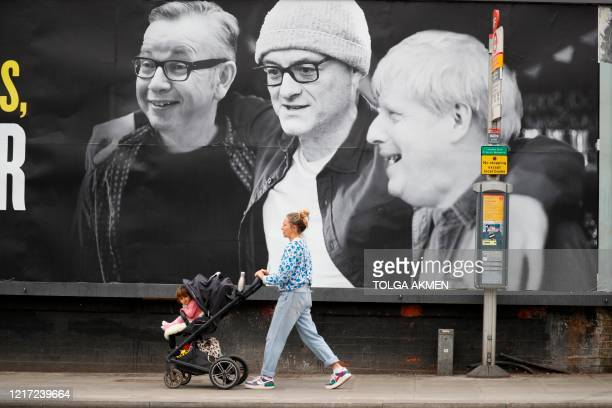 Woman wheels a pram past a billboard featuring Britain's Chancellor of the Duchy of Lancaster Michael Gove, Number 10 special advisor Dominic...