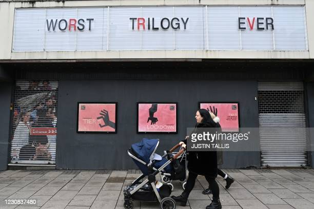 Woman wheels a pram past a shuttered cinema in Islington, north London on January 28 during the country's second national lockdown due to the novel...