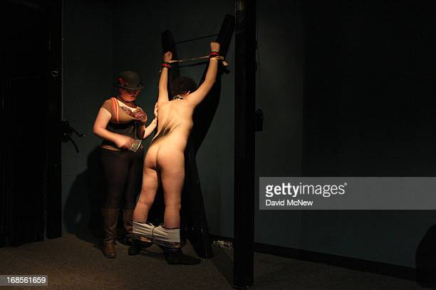 A woman whips a voluntarily submissive man tied who is up at a dungeon party during the domination convention DomCon LA in the early morning hours of...