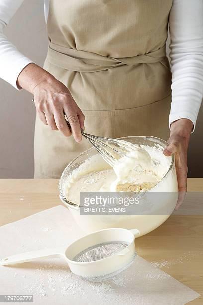 woman whisking cream by hand - female whipping stock-fotos und bilder