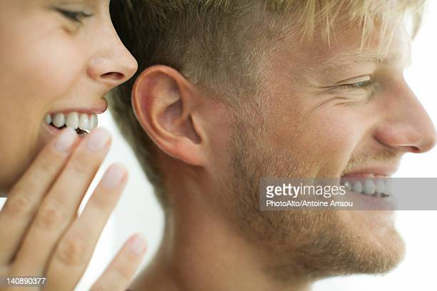 Woman whispering in man's ear, close-up
