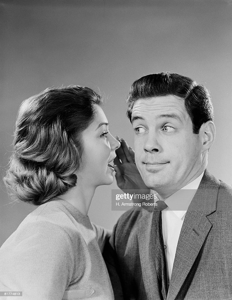 Woman whispering into man's ear, man pulling funny face. : Foto de stock