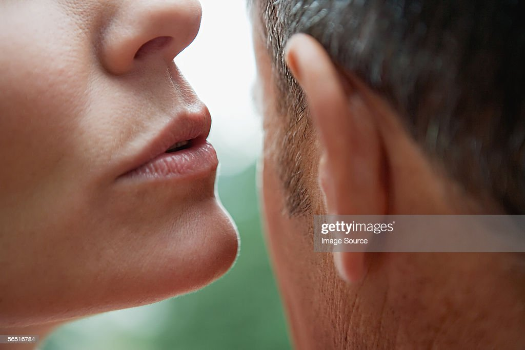 Woman whispering into man's ear : Stock Photo