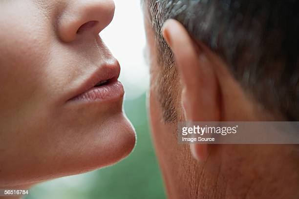 woman whispering into man's ear - ear stock pictures, royalty-free photos & images