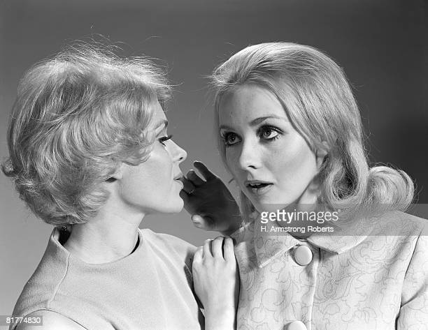 Woman whispering secret into another woman's ear.
