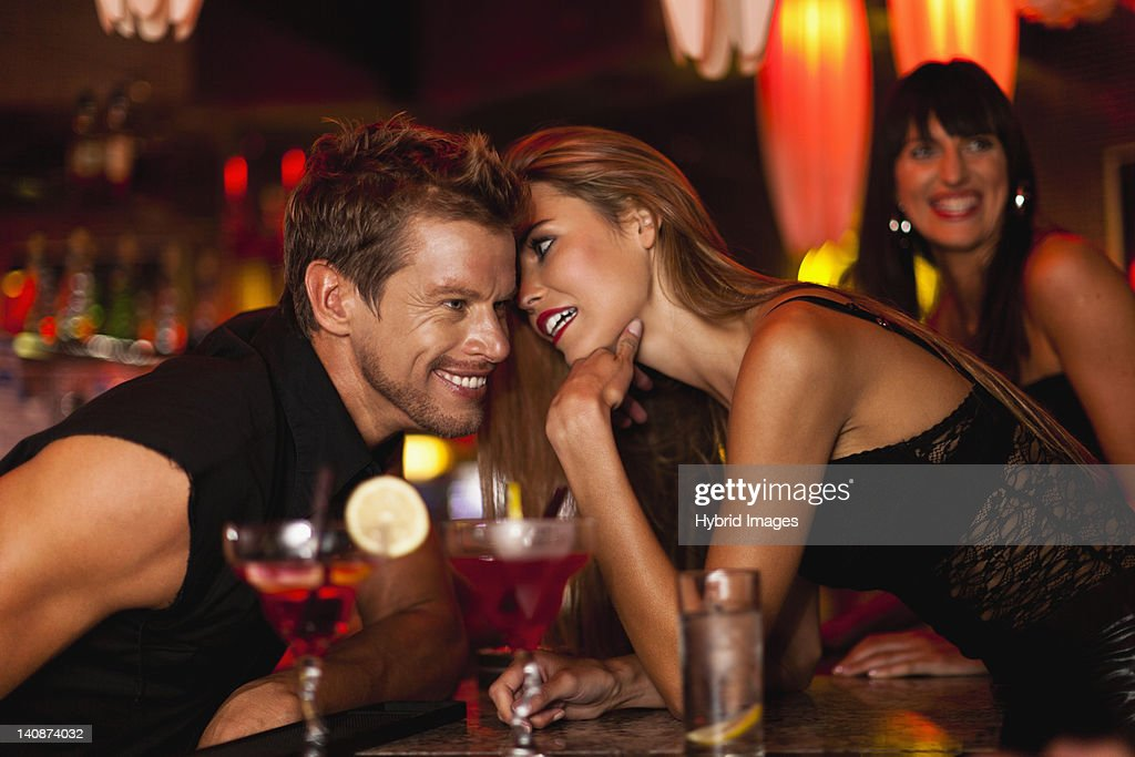 Woman whispering to bartender : Stock Photo