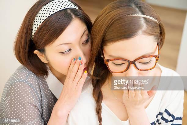 woman whispering to friend - チャタム ストックフォトと画像