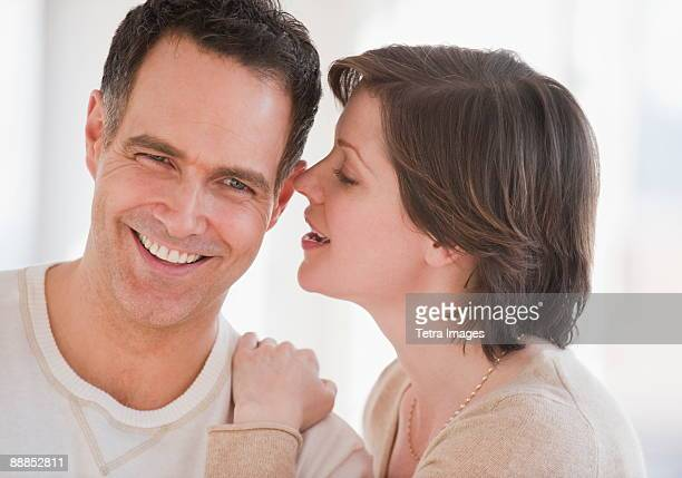 Woman whispering to mans ear