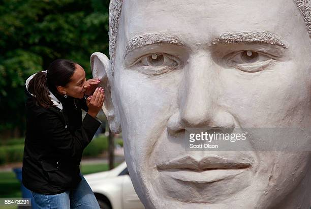 Woman whispers into the ear of a bust of President Barack Obama June 13, 2009 in Chicago, Illinois. The sculpture, created by Houston artist David...
