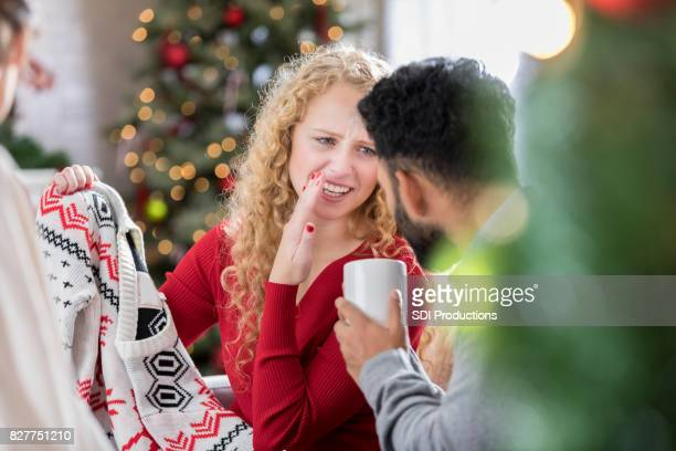woman whispers something to boyfriend after receiving ugly christmas sweater - ugly asian woman stock photos and pictures