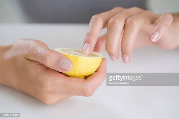 Woman whitening her fingernails with a lemon