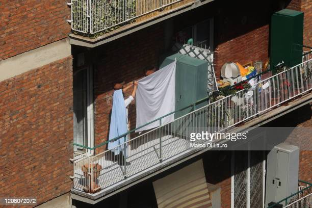 A woman who appears to have a veil is spreading her sheets to dry on her balcony during lockdown on March 23 2020 in Rome Italy As Italy extends its...