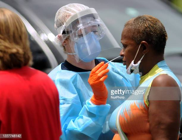 Woman who arrived on foot is tested for COVID-19 at a drive-thru testing site at Camping World Stadium on July 22, 2020 in Orlando, Florida. On...