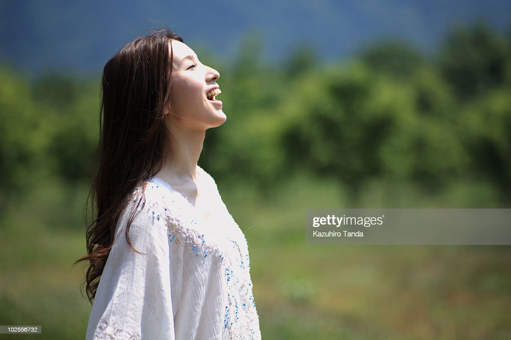 Woman who calls someone in field : Stock Photo