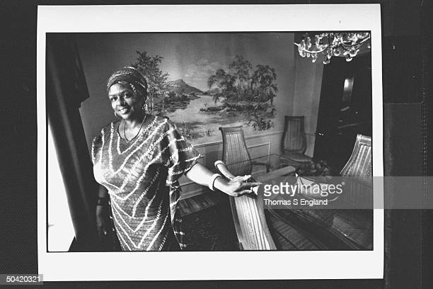 Woman who cooked last supper for Martin Luther King Jr Adjua Abi Naantaanbuu posing by window of dining room dressed in African garb