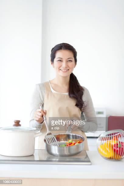 料理をする女性 - エプロン ストックフォトと画像