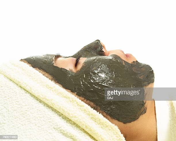 woman who does face masks, side view - estetista foto e immagini stock