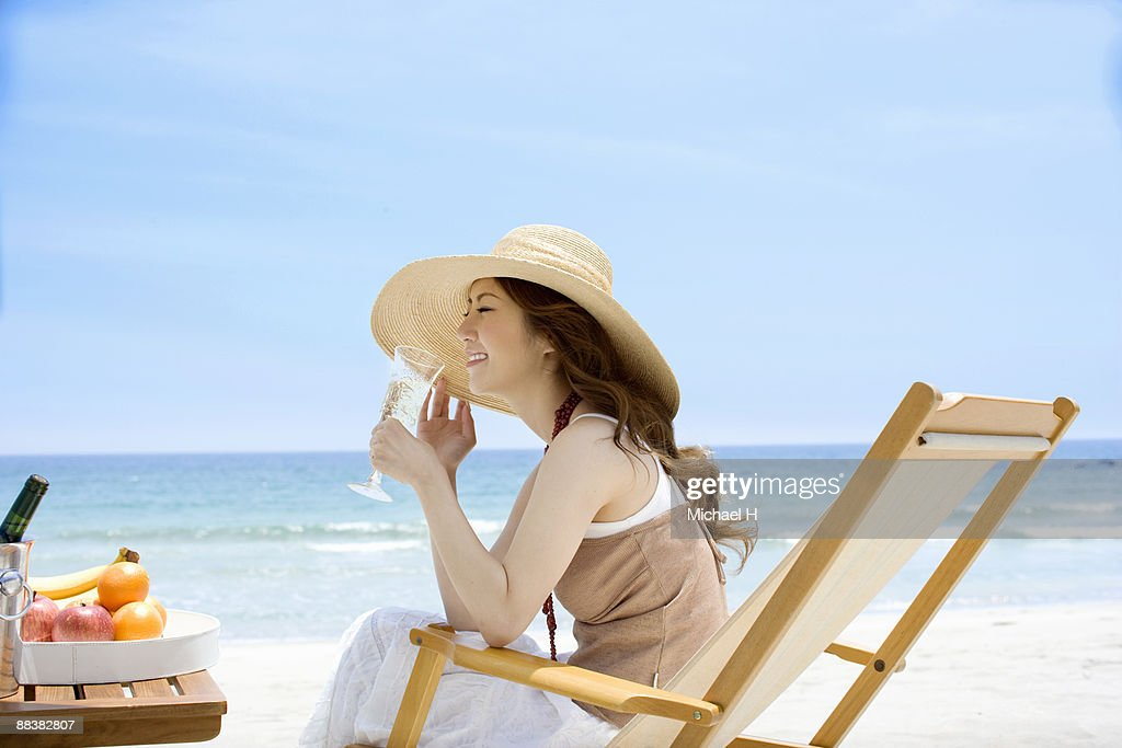 Woman who drinks champagne on beach : Stock Photo