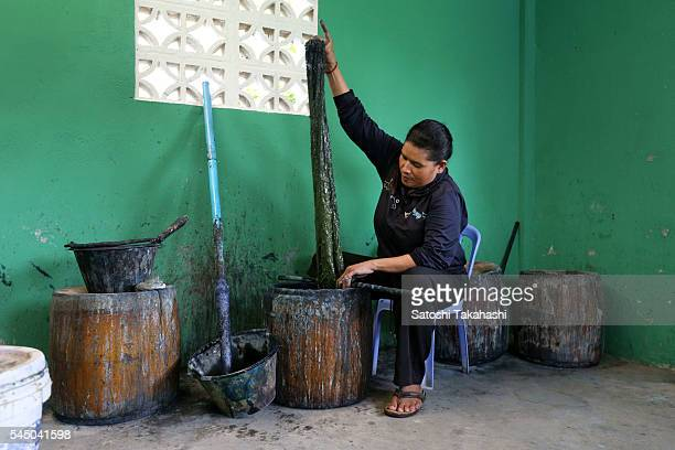 CYK'S WEAVING TRAINING CENTER TAKEO PROVINCE CAMBODIA A woman who dyes raw silk into indigo for the revival of Cambodia's traditional silk fabric...
