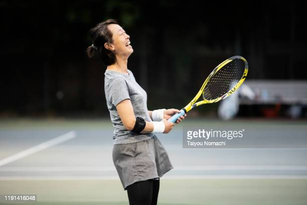 a woman who enjoys tennis at night - tennis stock pictures, royalty-free photos & images