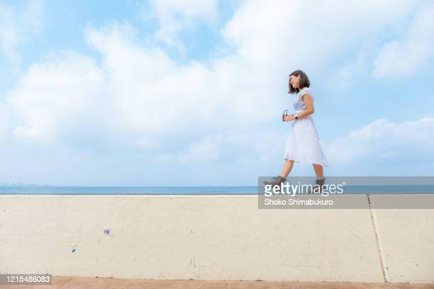 a woman who enjoys traveling alone. a beautiful seaside tourist destination in japan. casual travel. - levee stock pictures, royalty-free photos & images