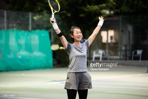 a woman who expresses joy in winning a tennis game - tennis stock pictures, royalty-free photos & images