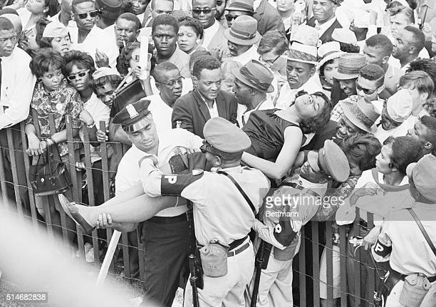 A woman who fainted in the crowd during the March on Washington is aided by police officers and National Guardsmen
