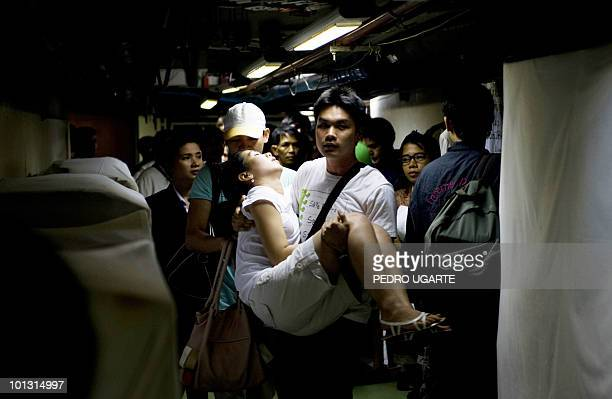 Woman who fainted is carried away as guests make their way through the basement of the Dusit Thani hotel as they are evacuated after an explosion and...