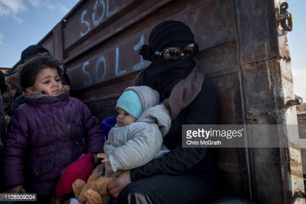 Woman who fled fighting in Bagouz sits with her children on a truck after being screened by members of the Syrian Democratic Forces at a makeshift...